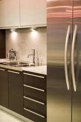 A contemporary kitchen with stainless steel appliances and dark wood fittings