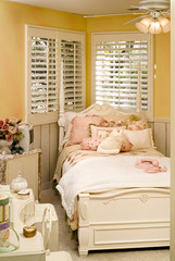 A telephone and several cushions are kept on the bed in a cozy bedroom
