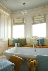 A white bathtub is seen against a window seat in a bathroom