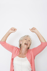 A senior woman dancing to music on an mp3 player