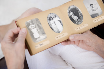 A senior woman looking at old family photographs