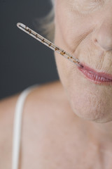 A senior woman with a thermometer in her mouth