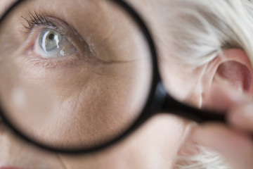 A senior woman looking through magnifying glass