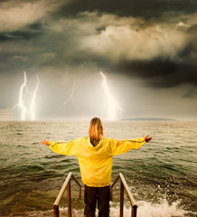 .Brave woman greeting stormy ocean