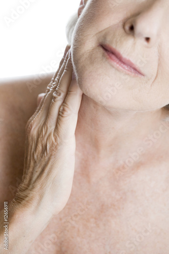 A senior woman touching her neck