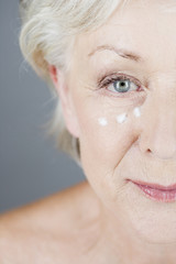 A senior woman applying eye cream