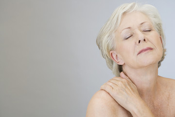 A senior woman with shoulder tension or back ache
