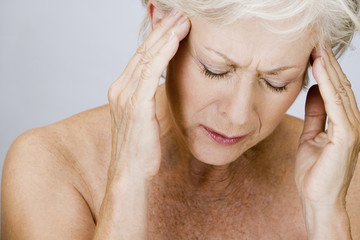 A senior woman with a headache, touching temples