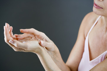 A middle-aged woman applying hand cream