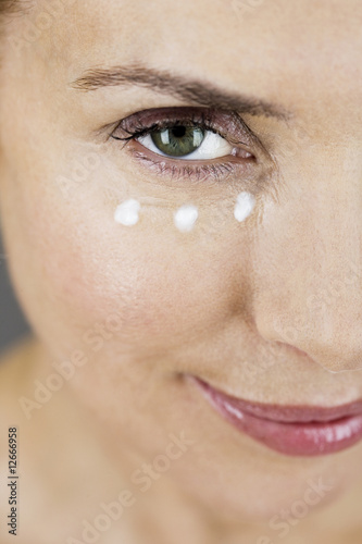 A middle-aged woman applying eye cream