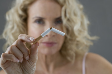 A middle-aged woman breaking a cigarette in half