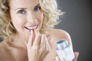 A middle-aged woman holding a vitamin supplement capsule
