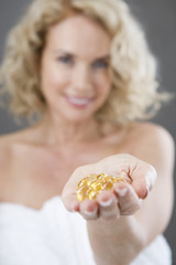 A woman holding a handful of vitamin supplement capsules