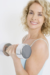 A middle-aged woman working out with free weights