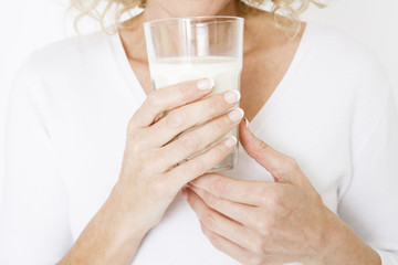 A middle-aged woman holding a glass of milk