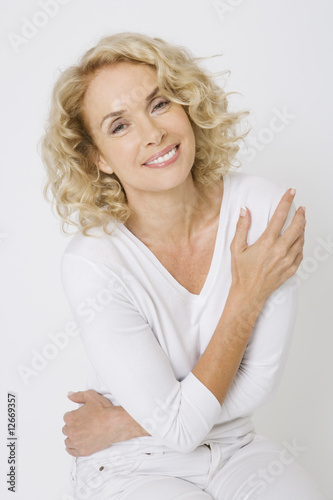 A confident and attractive middle-aged woman in white, smiling