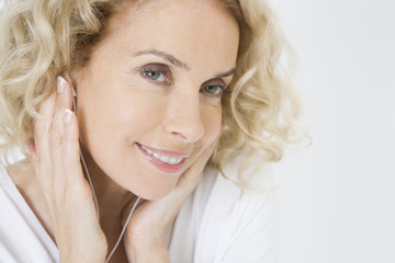 A middle-aged woman listening to mp3 music player