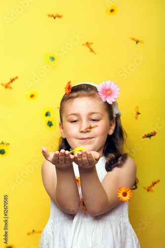 smiling beautiful  young girl with falling flowers at spring
