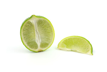 Half of lime with a separate slice laying beside.