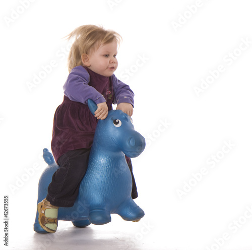 small jumping on plastic donkey young girl