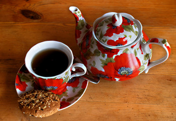 Cookies, cup and teapot on a wooden table