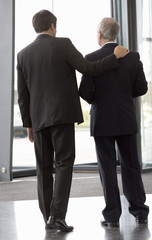 Two businessmen leaving an office building