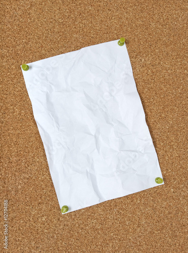 Crumpled paper pinned to corkboard