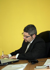 Young businessman writing at desk