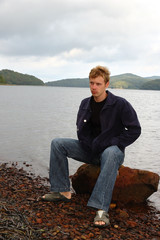 Young blond man on sea shingle beach.