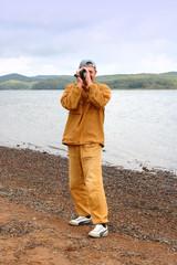 Cameraman on sea shingle beach.