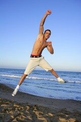 young man jumping on the blue beach