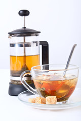a cup of green tea with chrysanthemum and a french press
