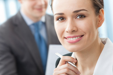 Portrait of businesswoman and colleague on background