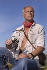 Explorer posing outdoors with is binoculars