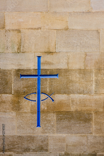 Engraving of a cross and fish in a stone wall