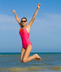 Girl in swimsuit jumping on a beach