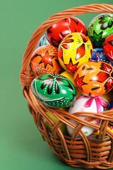 Easter Eggs in wicker basket on green