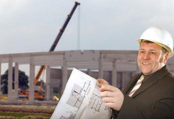 Ingenieur mit Bauplan und Helm auf der Baustelle