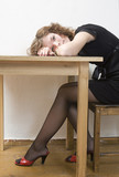 upset girl in black dress and red shoes put her head down table. poster