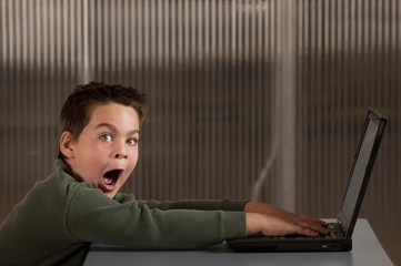 Shocked boy with a laptop computer