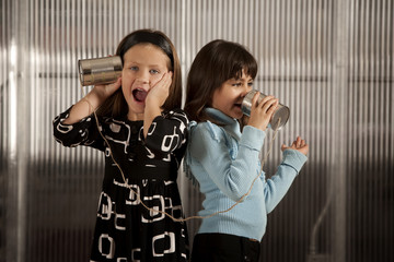 Little girl getting shocking message on tin can phone