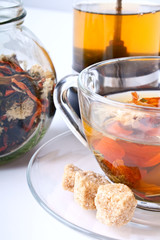 a cup of flower tea with chrysanthemum, dry tea in a jar and a f