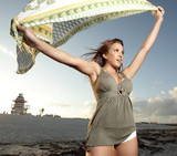 Woman holding a sarong in the wind poster