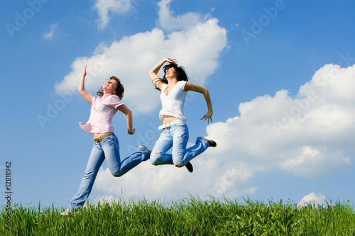 two happy women jumping on the green grass
