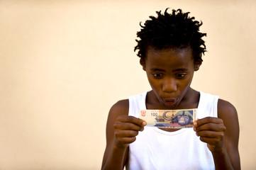 Junge schaut auf Geldschein