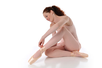 Ballerina putting her shoes on