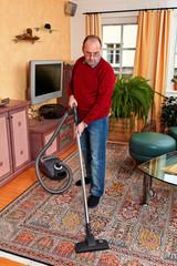 Mann bei Hausarbeit mit Staubsauger