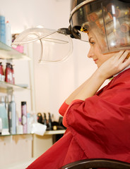 Young woman drying her hair in beauty salon