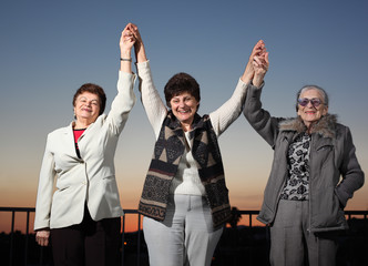 Three united women raising hands