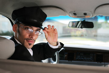 Portrait of a chauffeur sitting in a car saluting a viewer